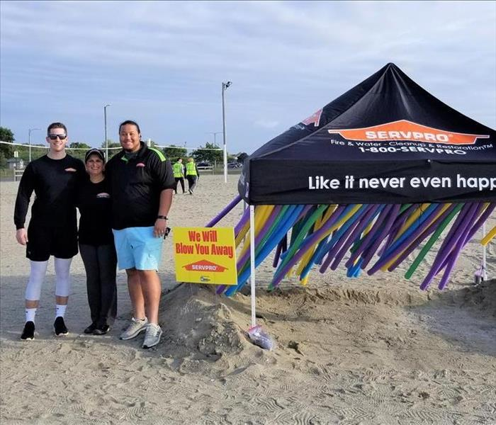 3 people standing in front of a servpro tent with obstacle course on the beach