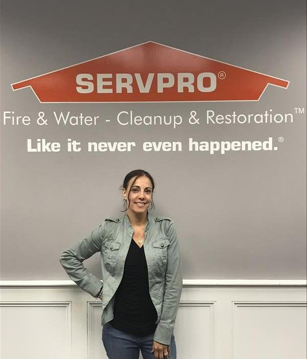 Woman standing in front of a SERVPRO sign