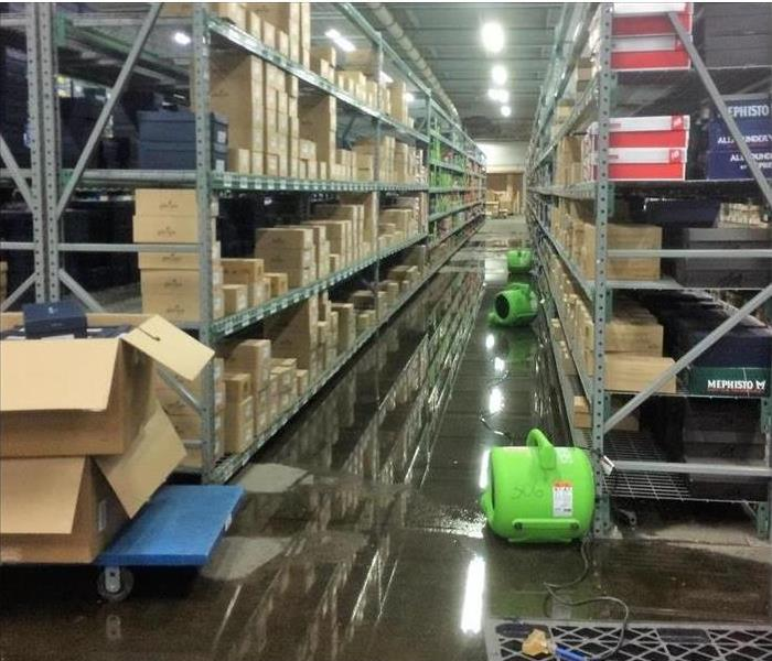 a flooded warehouse with shelving and servpro dehumidifiers on the floor