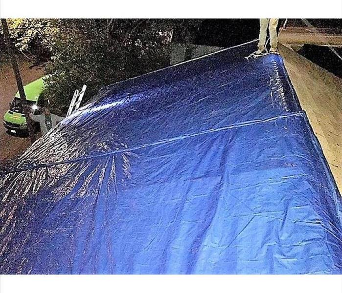 house at night with a tarp over the roof and SERVPRO truck