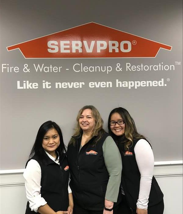 three ladies standing in front of a SERVPRO sign