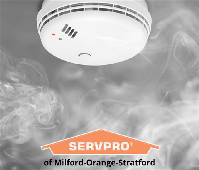 smoke detector on a ceiling with smoke rising it around it