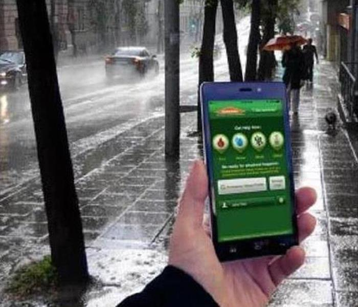 a hand holding a phone with a SERVPRO app on it on a rainy street