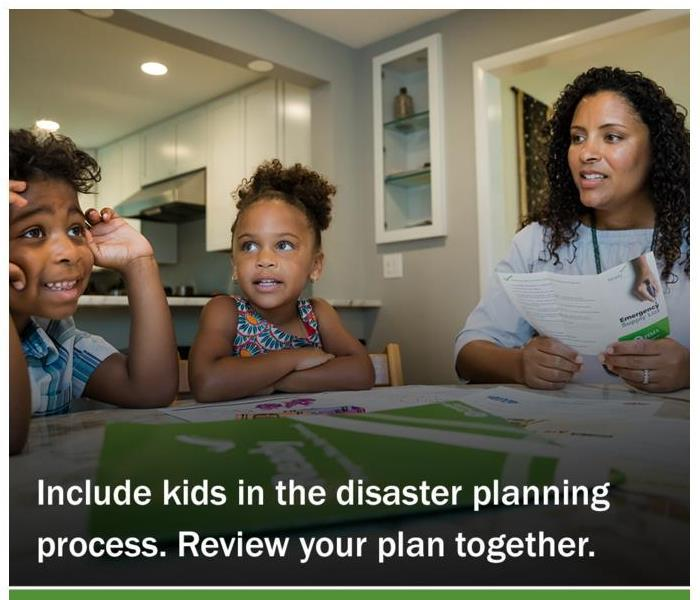 children sitting at the table with mother looking at emergency planning brochure