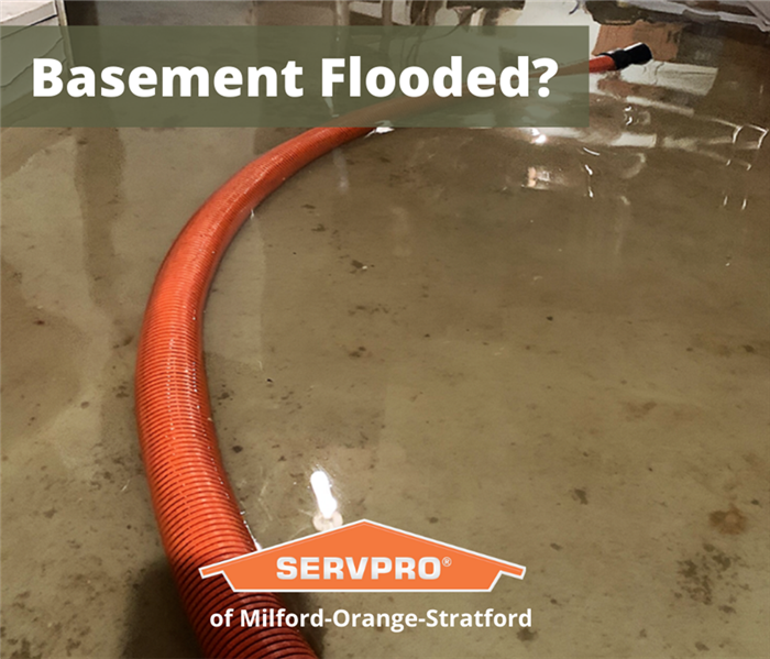 flooded basement with orange hose running through it
